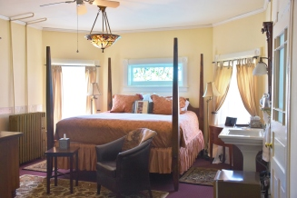 Another comfy bedroom with a stained glass window.