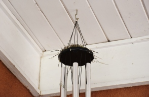 A small bird's nest sits atop a wind chime. Lovely!